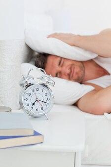 目覚める前に彼のベッドの中で苛立つ男