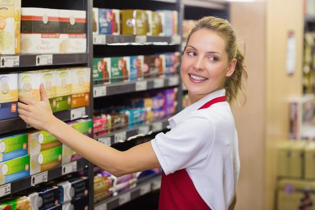 Улыбаясь блондинка работник, взяв продукт в полке