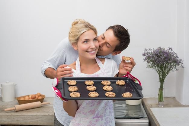 彼女はキッチンで新鮮な焼きたてのクッキーを握っているように、女性の頬にキスする男