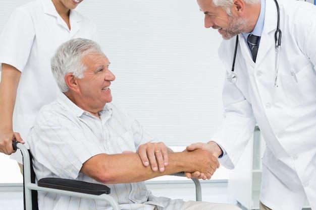 シニアの患者と医者の握手