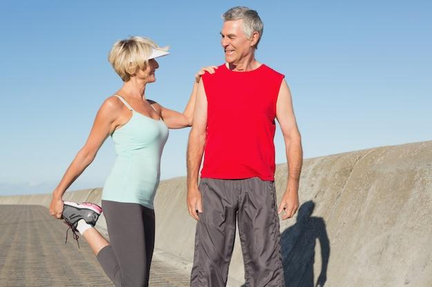 ジョギングする前に伸びている活発なシニアカップル