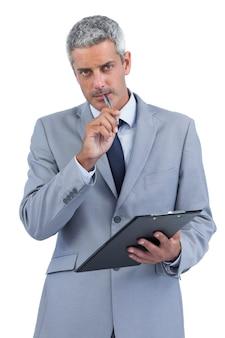 クリップボードを持ってノートを取る挑発的なビジネスマン