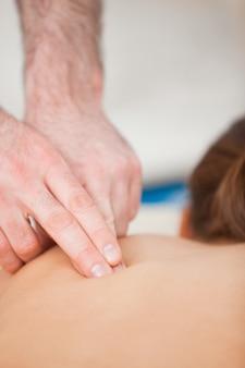 医者は患者の背中をマッサージするために彼の指を使って
