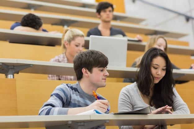 講義室に座って働く学生