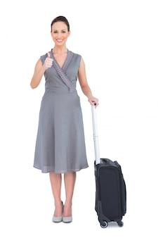 彼女のスーツケースで陽気な豪華な女性が親指をあげて