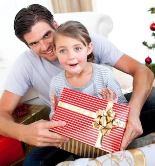 彼女の父親がクリスマスプレゼントを受け取った幸せな少女