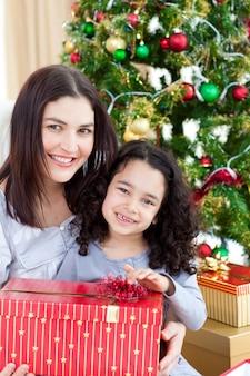 母親と娘が家でクリスマスプレゼントをしています