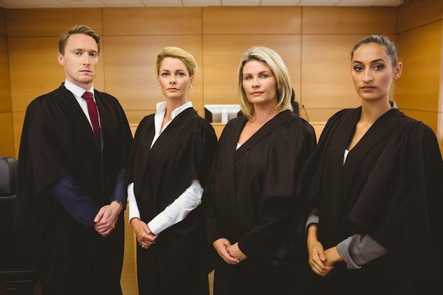 Четверо серьезных судей, стоящих во время ношения одежды