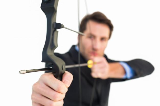 弓と矢を撮影しているビジネスマンの近く