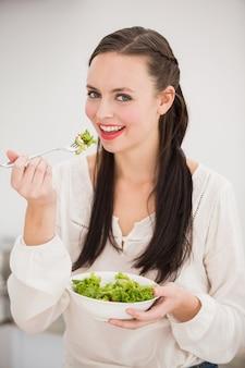 健康なサラダを準備するかなりのブルネット