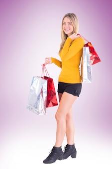 スタイリッシュなブロンド、ビネットの背景にショッピングバッグで笑う