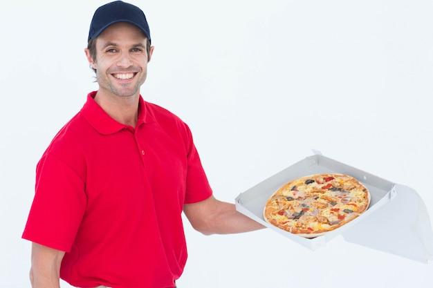 新鮮なピザを持っている幸せな配達人