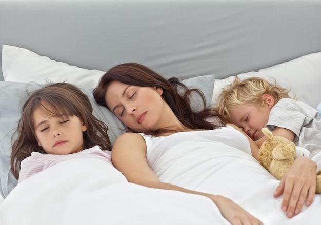 彼女のベッドの上で母親と寝る愛らしい子供たち