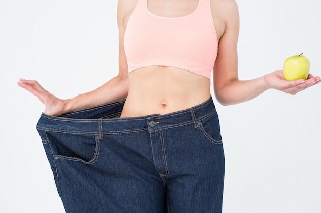 重量を失った後に彼女の腰を示す女性