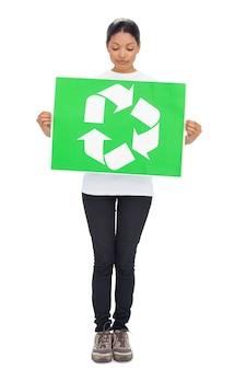リサイクルサインを持っているボランティアの若い女性