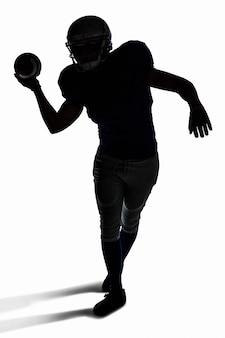 Американский футболист бросает мяч