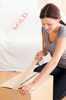 Женщина готовит картон для перевозки