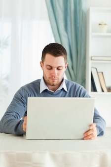 彼のホームオフィスにノートパソコンを持っている男