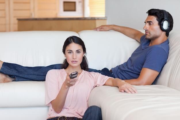 Женщина смотрит телевизор, пока ее парень слушает музыку