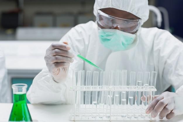 緑色の液体で試験管に充填する化学者