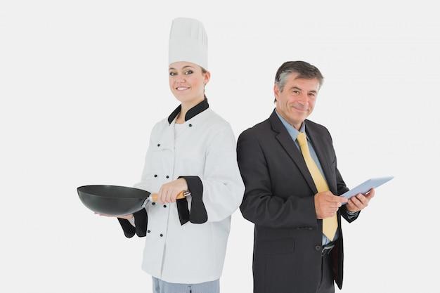 Бизнесмен, проведение цифровой планшет и женский шеф-повар с сковорода