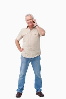 彼の携帯電話で話す笑顔の成熟した男性