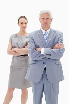 真剣な白髪のビジネスマン、彼の後ろに女性が腕を横切る