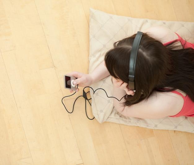 床に横たわっているブルネットの女性の聴く音楽