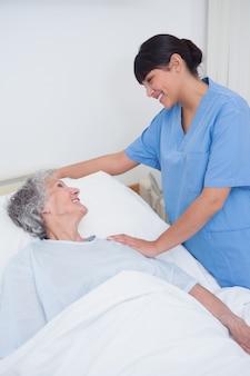 Медсестра, касаясь плеча пациента