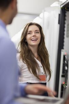 Женщина, работающая на серверах, смеется с коллегой