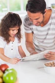 お父さんと娘が新聞を読んでいる
