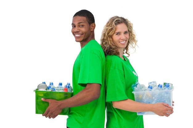 リサイクル可能な箱を持ち、背中合わせに立っている陽気な環境活動家
