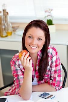 キッチンに座っているリンゴを持っている喜んでいる女性