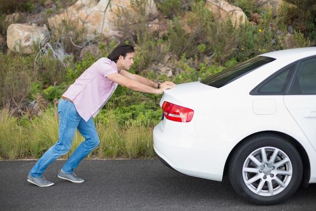 車の故障後に車を押す男