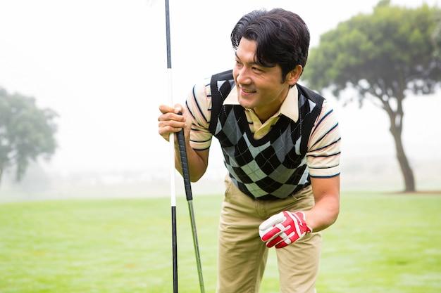 ゴルフボールとクラブを保持するゴルファー
