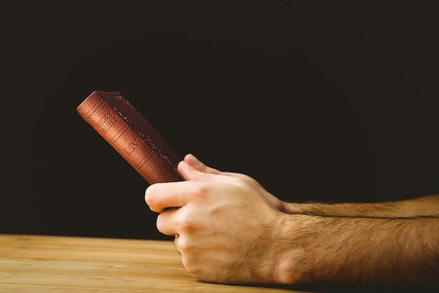 彼の聖書で祈っている男