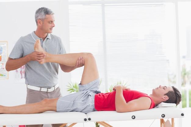 彼の患者に足のマッサージをしている理学療法士