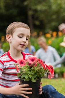 花の鍋で座っている若い男の子
