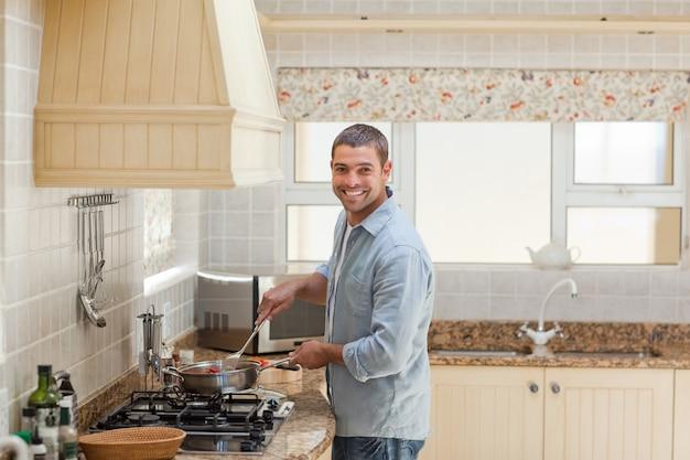 キッチンで調理するハンサムな男