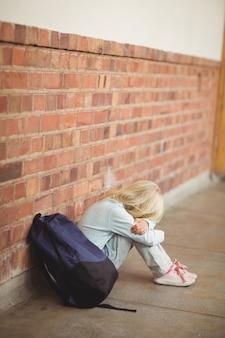 悲しい弟子が一人で地面に座っている