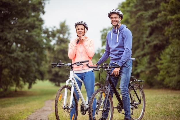 田舎で自転車に乗っている幸せなカップル