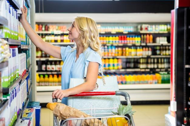 笑顔の女性は、酪農製品を選ぶ