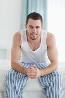 彼のベッドに座っている笑っている男の肖像