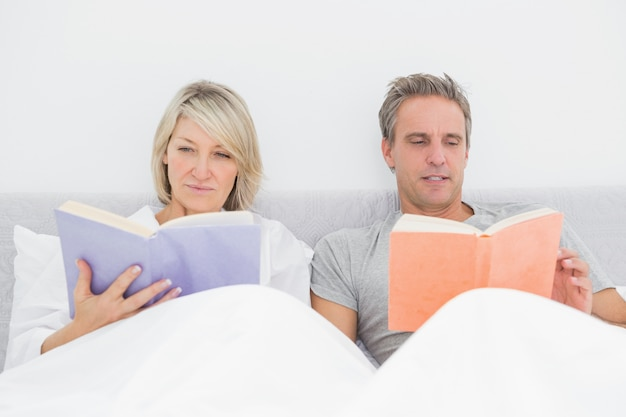 ベッドでリラックスしたカップルの読書