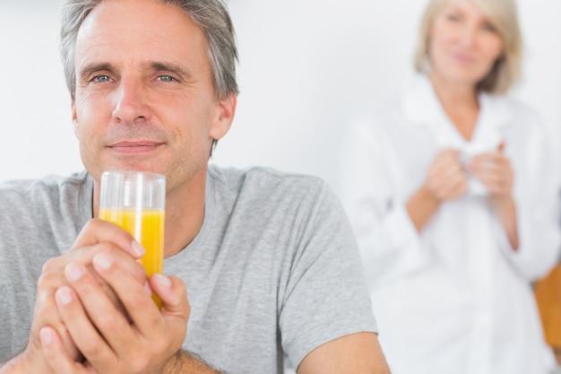 キッチンでオレンジジュースを飲む幸せな男