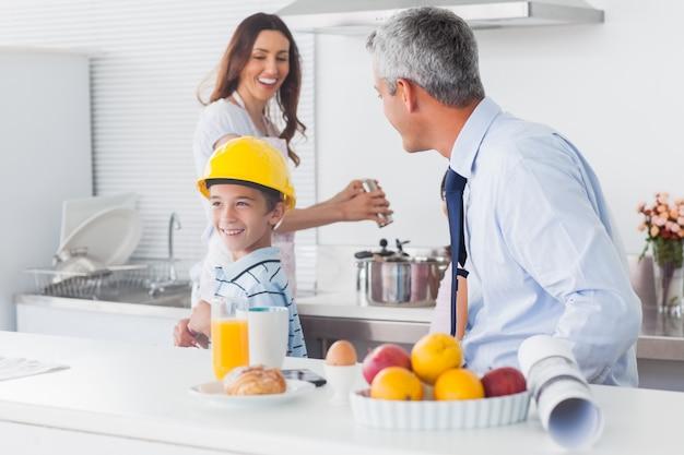 両親が笑っている父親のハード帽子を試している少年