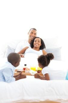 Радостная семья, завтракающая в спальне