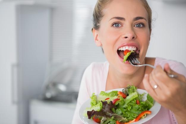 サラダを食べながらカジュアルなブロンドポーズ