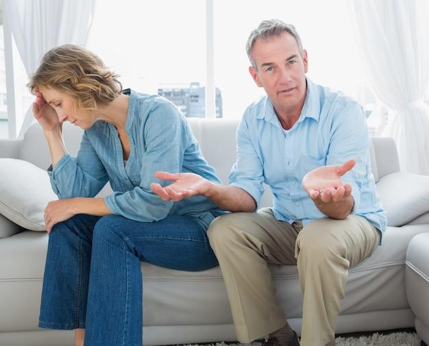 身に着けている男とソファに座っている中年のカップルを信じて