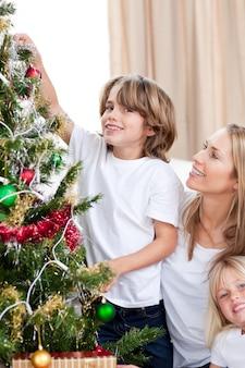 母と子供たちがクリスマスツリーを飾る